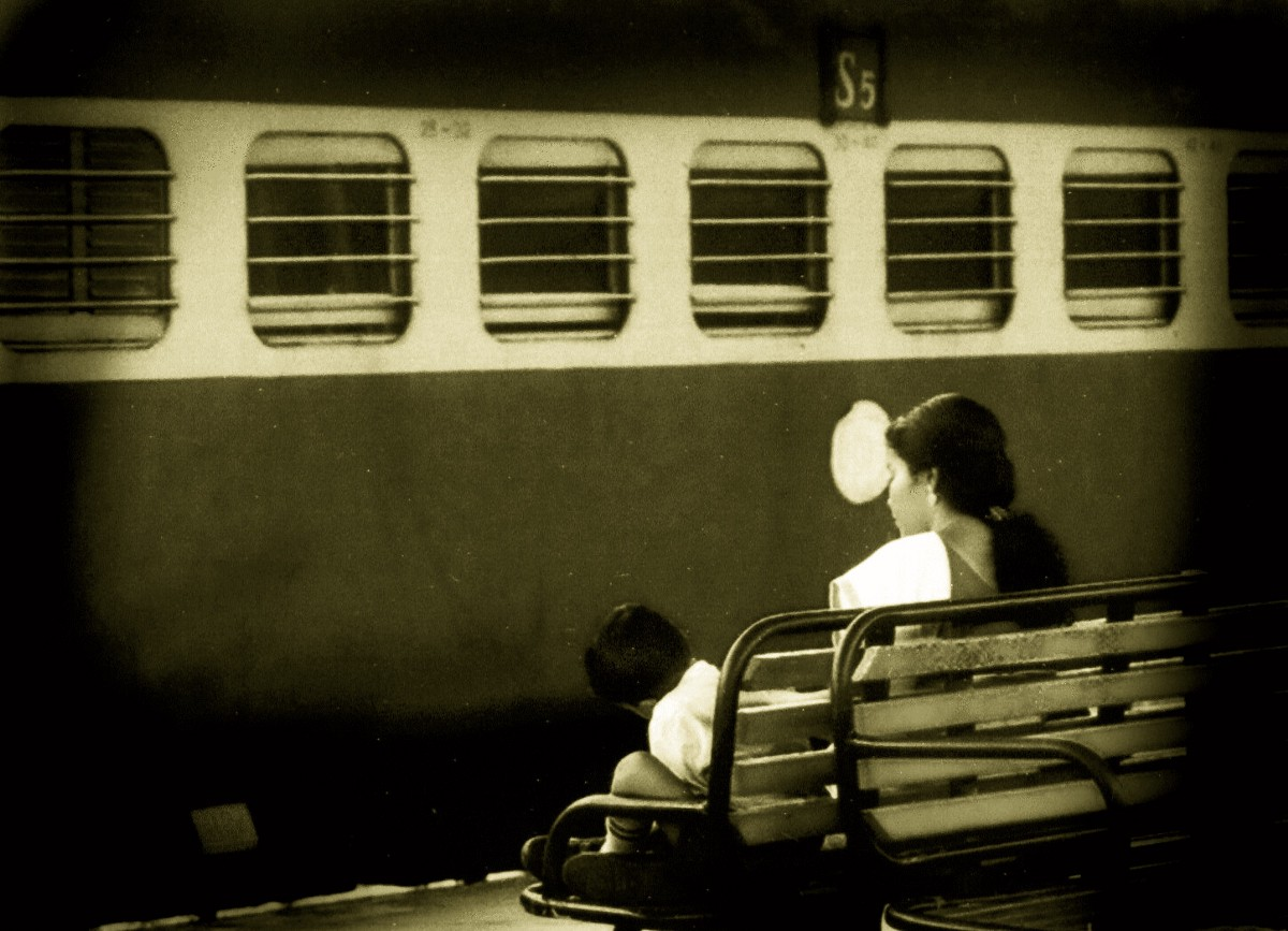 Monochrome image of a train at a station, with a mother and son on a platform bench.